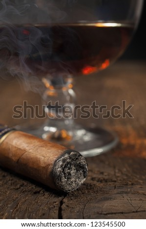 smoking cigar with a glass of brandy in the background