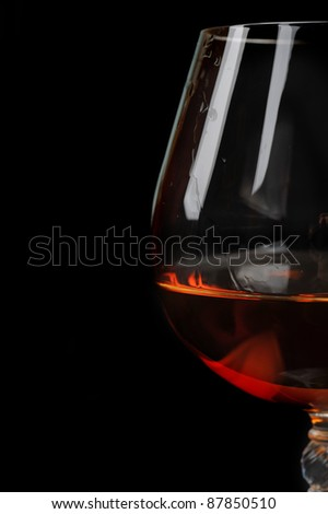 snifter of  brandy in  elegant  glass.  black background - stock photo