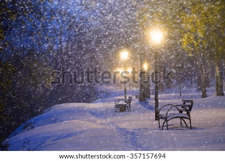 Snow-covered bench and path in winter park. - stock photo