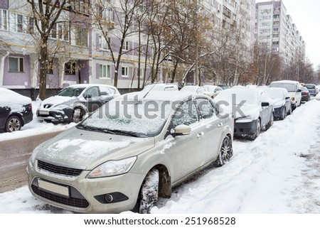 snow covered cars in parking lot  - stock photo