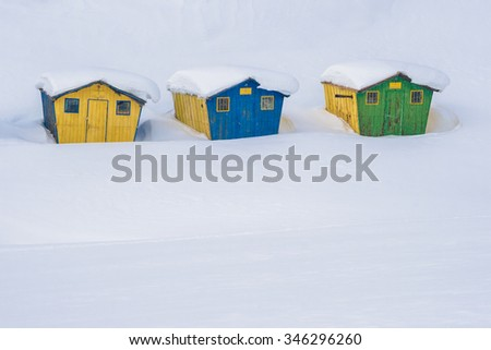 Snow-covered winter mountain landscape with abandoned colorful wooden huts - stock photo