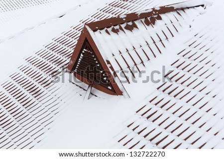 snow on metal tiles roofing in winter - stock photo