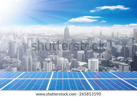 solar energy panels on high building against beautiful sky with ecology concept - stock photo