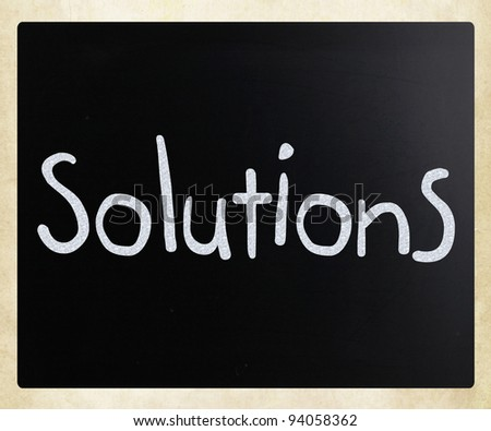 """Solutions"" handwritten with white chalk on a blackboard - stock photo"