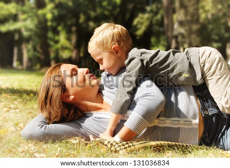 Son and mother tender hugs at the sunny day in park - stock photo