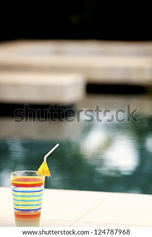 soothing abstract background with a punch of color in a striped tropical glass in the foreground - stock photo