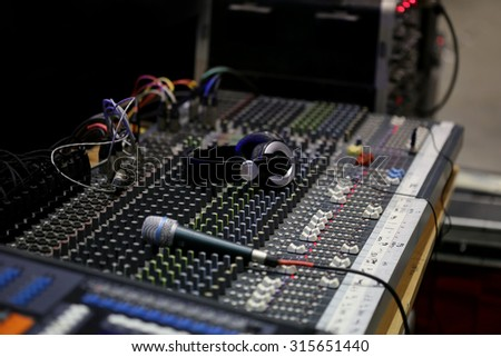 sound mixer board and headphone, Audio mixer mixing board fader and knobs, Sound mixer, low angle shot with shallow DOF, useful for various music and sound themes, room - stock photo