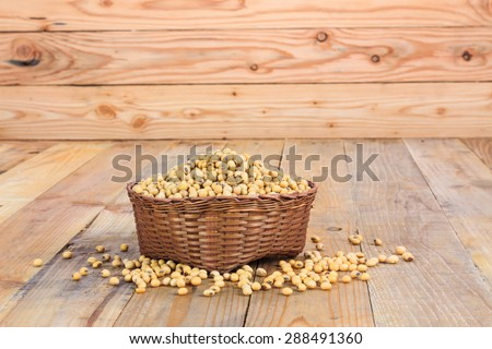 soya beans in the basket on wooden background - stock photo