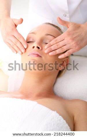 Spa.Beautician beautiful woman massaging her temples . Woman in a beauty salon. Masseur massaging a woman in a spa. - stock photo