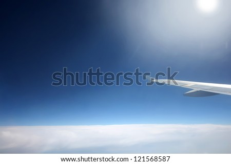 Space sky with aircraft wing. 	View from the plain on white condensed clouds and space above the clouds