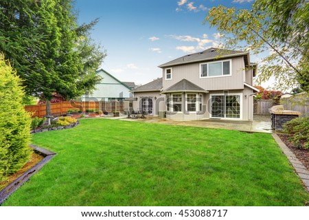 Spacious backyard garden of large beige house with green lawn and Cozy patio area.