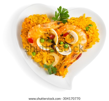 Spanish dish paella with seafood on a white heart shaped dish isolated on a white background. Top view. - stock photo