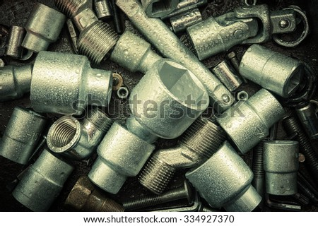 Spanner wrench heads, nuts and bolts on a dark scratched metal background. Toned. - stock photo
