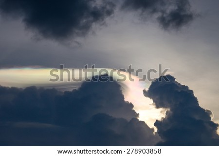 Spectacular rainbow light behind dark clouds in the evening - stock photo