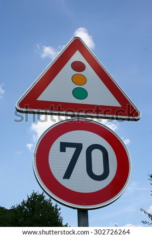70 speed limit road sign, with traffic light warning, Germany. - stock photo