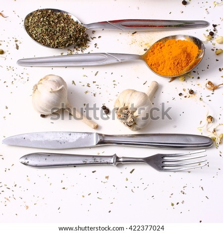 Spices and cutlery on a white table. - stock photo