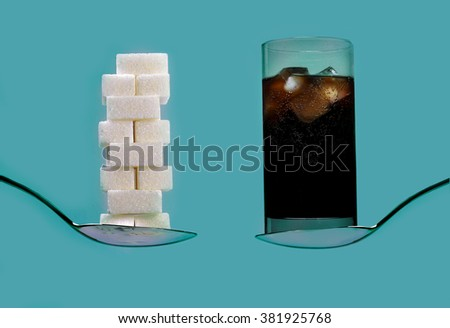 spoon with stack of sugar cubes piled  compared with cola refresh drink in sweet excess calories content,  diet and glucose addiction concept isolated on blue background - stock photo