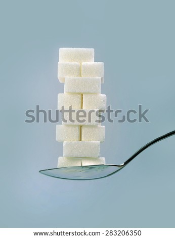 spoon with stack of sugar cubes piled in sweet excess, unhealthy nutrition, diet and sugar addiction concept isolated on blue background - stock photo