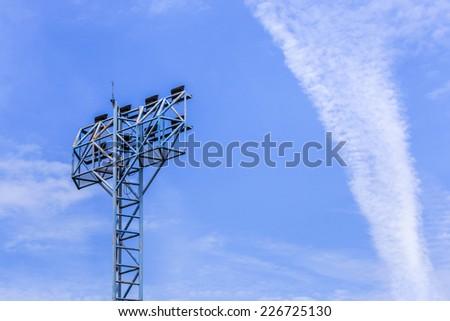 spotlights pillar in stadium on blue sky background - stock photo
