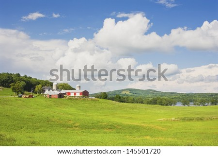 Spring farm and hay field with blue sky and clouds in maine. - stock photo