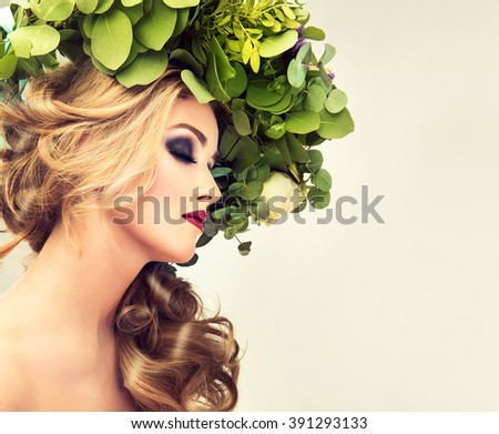 Spring  girl. Beautiful model with flower wreath on her head . Makeup smoky eyes . Summer girl with trendy makeup . Hairstyle curly ponytail with flowers in her hair .