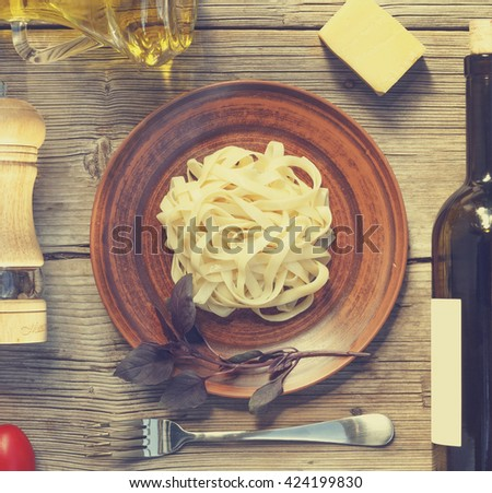 square frame. Wine. Pasta. Cherry tomatoes. Top view. Closeup. Spices. Italian food ingredients on wooden background. Mock Up.  - stock photo