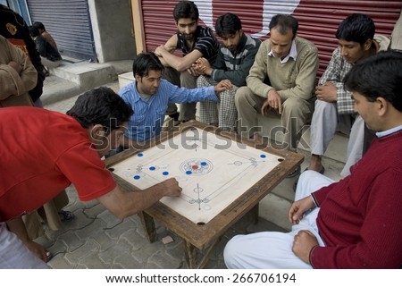 "SRINAGAR, INDIA - MAY 6: Unidentified Kashmiri men play traditional board game ""carrom"" during city strike, Srinagar, Kashmir, India, May 6, 2009. Strike was dedicated to the parliamentary election. - stock photo"