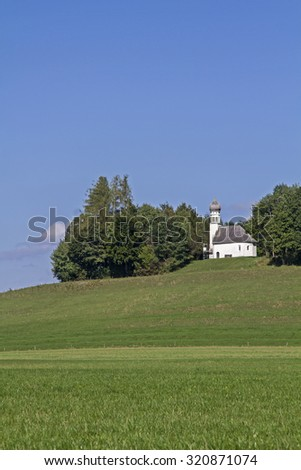St. Georg in Ascholding - small legendary church on a hill at Ascholding - stock photo