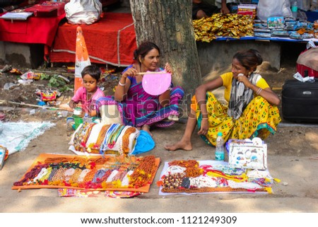 21st June 2018, Guwahati, Assam, India. Two women with a kid selling artificial jewelry during Ambubashi mela in the street of Kamakhya Temple in Assam, India.