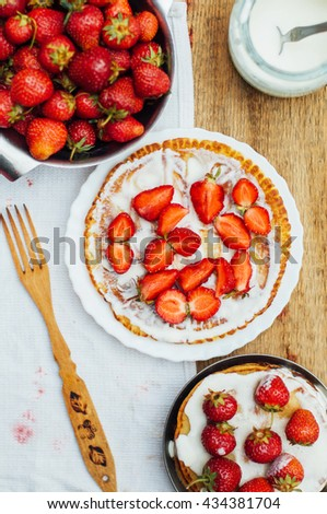 Stack of pancakes with fresh strawberry and balsamic glase in frying pan on wooden table. Rustic style  - stock photo
