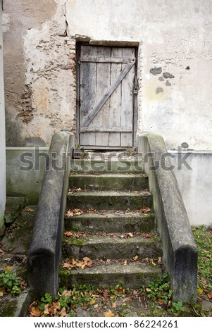 Stairs and wooden door in an old wall