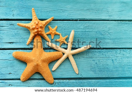 Starfish on blue wooden background. Top view with copy space. Summer concept.