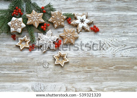 Stars gingerbread  with red berries on christmas tree on wooden background