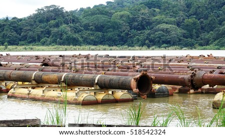 Steel pipe floating on canal waters use to help dredge the Panama Canal