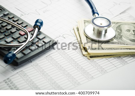 Stethoscope and calculator symbol for health care costs or medical insurance  - stock photo