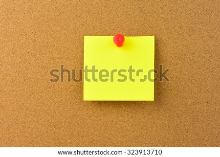 Sticky note with pin over wooden background