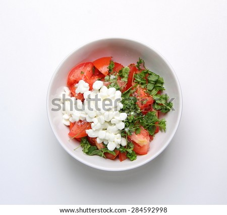 still life of lettuce with fresh tomatoes, parsley, basil, onion, with a handful of granulated cottage cheese in a white plate on a white background - stock photo