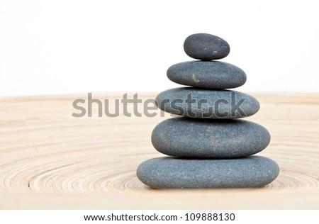Stone tower on a wooden board - stock photo