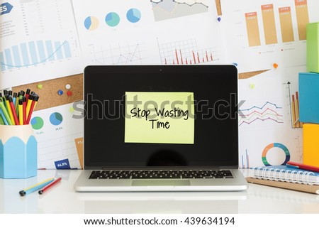 STOP WASTING TIME sticky note pasted on the laptop screen - stock photo