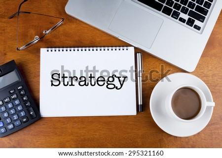 """""""Strategy"""" text on notebook with a cup of coffee, calculator, spectacle and laptop on desk - stock photo"""