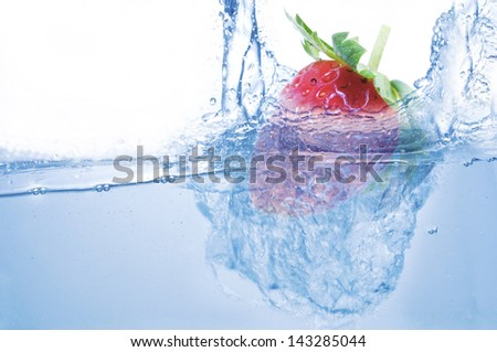 Strawberry  sinking in blue water - stock photo