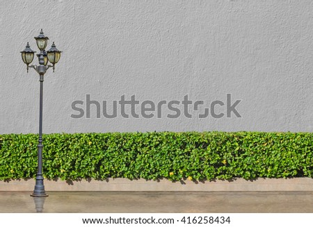 street electric lamp post at green bush fence and concrete floor on blue sky and white cloud background - stock photo