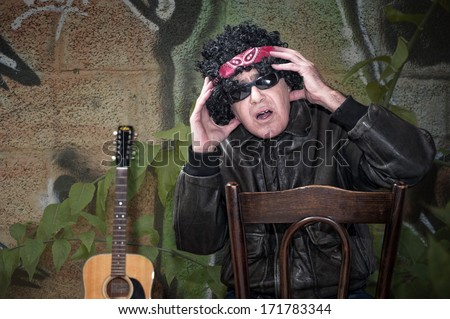 Stressed out rocker middle age man with bandana sitting on chair - stock photo