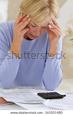 stressed senior woman is doing banking and administrative work at home