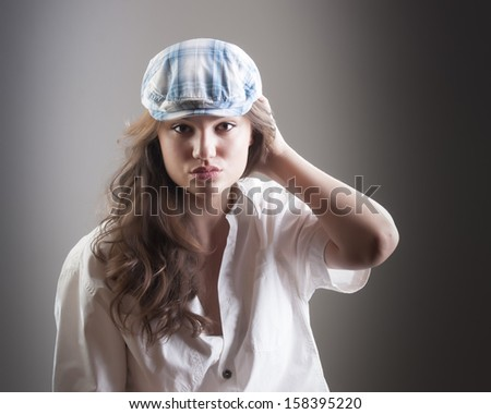 Studio portrait of young beautiful woman wearing sport hat  - stock photo