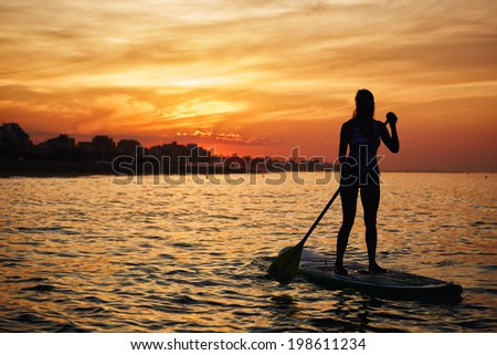 Stunning silhouette of a beautiful girl floating on on the surfboard at amazing orange sunset over the sea - stock photo