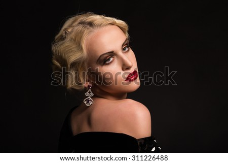 Stylish blonde on a black background. Portrait photo. Beautiful makeup. Beautiful dress and jewelry.