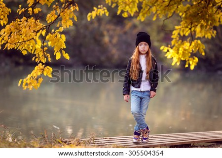 stylish red-haired girl in the autumn park - stock photo