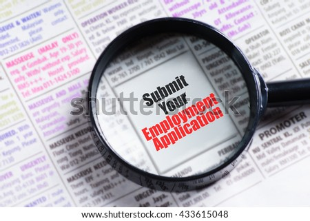 """Submit your employment application"" red and black text on blurry image of newspaper with magnifying glass on it symbolic as search"