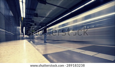 Subway station with passengers in motion blur - stock photo